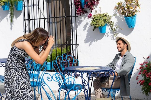Mulher em plano médio tirando fotos de um homem