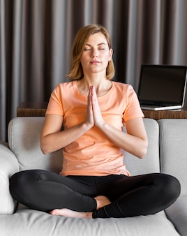 Mulher em plena cena no sofá meditando