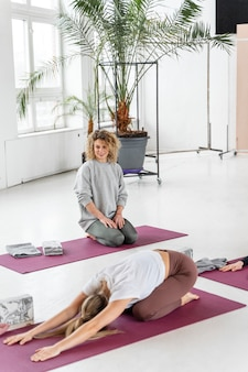 Mulher em plena cena no tapete de ioga alongando-se