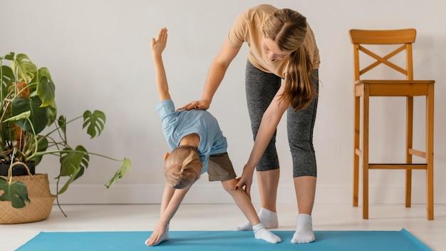 Mulher em pleno tiro ajudando criança a se exercitar