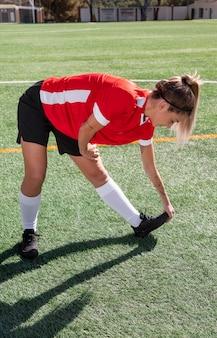 Mulher em pleno tiro no campo de futebol alongamento