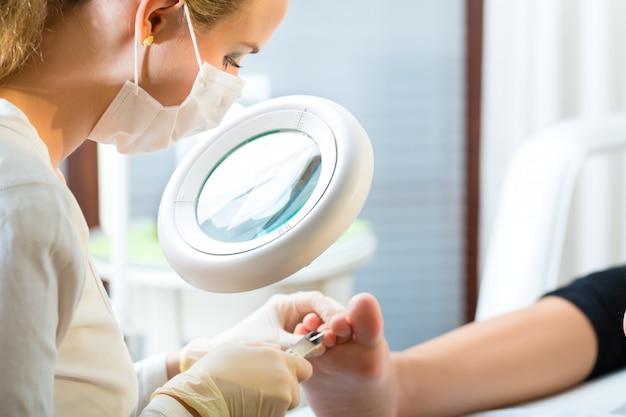 Mulher em podologia, recebendo pedicure