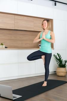 Mulher em pose de árvore enquanto pratica ioga online em casa