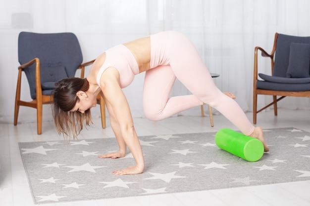 Mulher em pose de cachorro virado para baixo faz uma massagem nos pés com um rolo de espuma verde