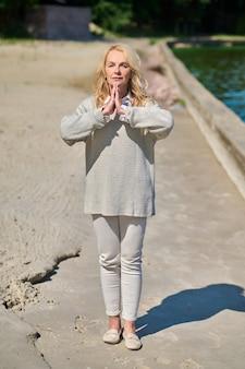 Mulher em pose de ioga à beira-mar