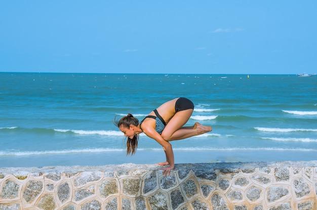 Mulher em pose de ioga na praia, retiro de ioga e treinamento.