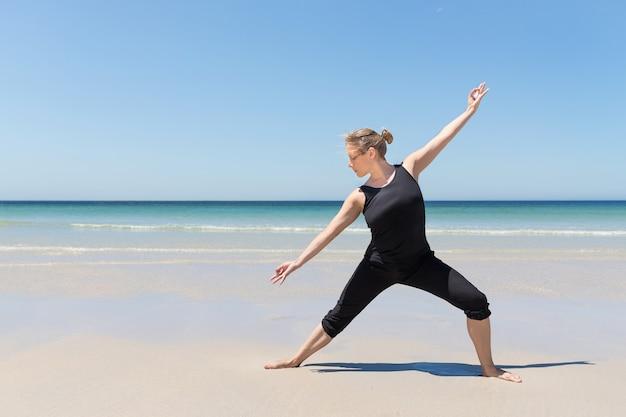Mulher em pose de meditação na praia
