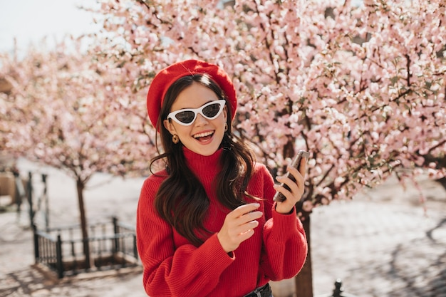 Mulher em poses de alto astral com telefone perto das flores de cerejeira. retrato de senhora de boina vermelha, suéter cashemere e óculos brancos no jardim na primavera