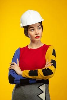 Mulher em poses de capacete de construção na câmera