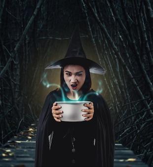 Mulher, em, pretas, assustador, bruxa, dia das bruxas, traje, segurando, assustador, bruxa, caldeirão, saída, em, escuro, f