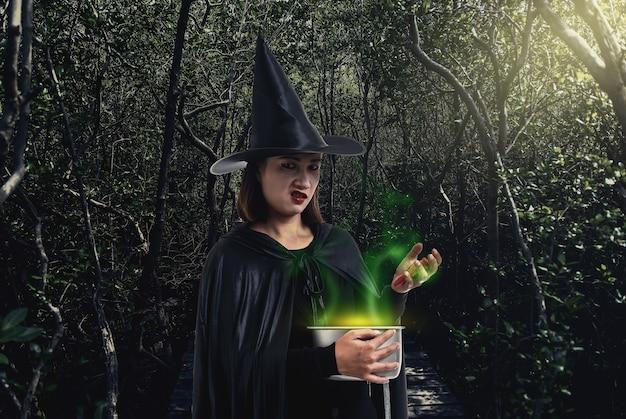 Mulher, em, pretas, assustador, bruxa, halloween traje, segurando, spooky, bruxa, caldeirão, em, um, escuro, para