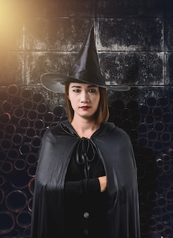 Mulher, em, pretas, assustador, bruxa, traje halloween, com, antigas, parede cimento