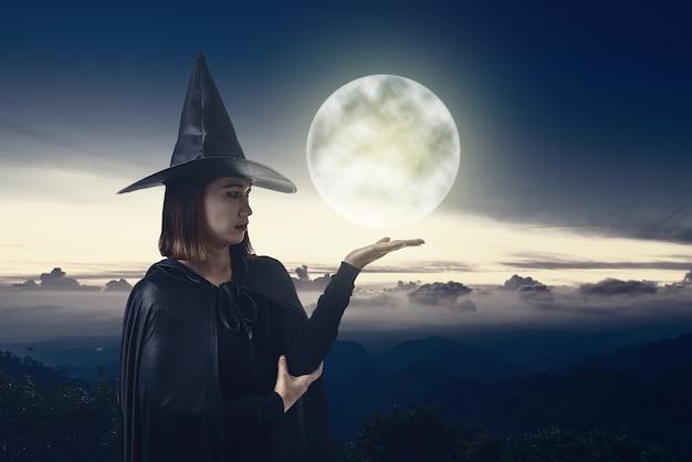 Mulher, em, pretas, assustador, bruxa, traje halloween, com, luar
