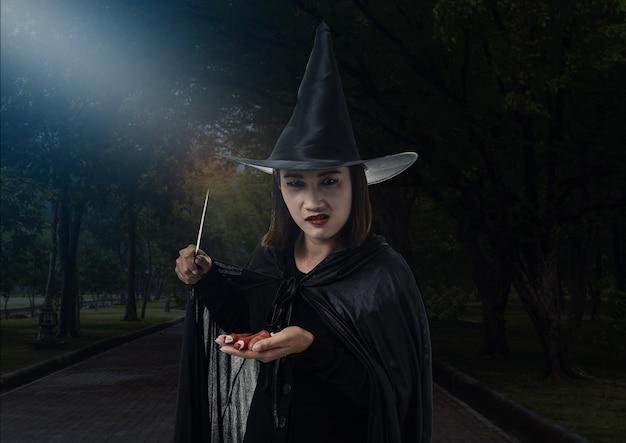 Mulher, em, pretas, assustador, bruxa, traje halloween, segurando, um, faca, com, luar, em, um, escuro, floresta