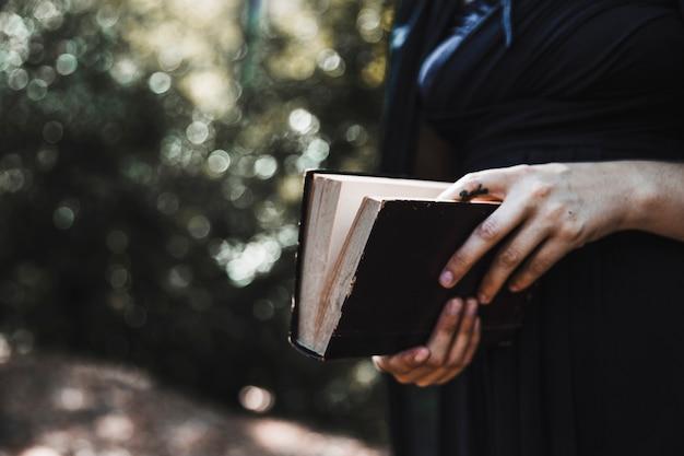 Mulher, em, pretas, segurando, livro, em, madeiras
