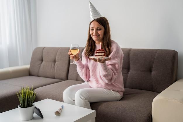 Mulher em quarentena com bolo e bebida comemorando aniversário