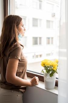 Mulher em quarentena com máscara médica olhando pela janela