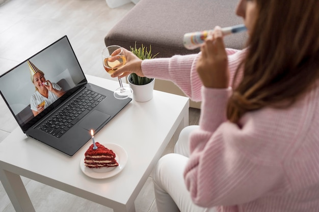 Mulher em quarentena comemorando aniversário com amigos no laptop e bebendo