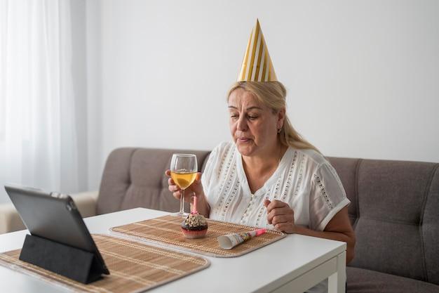 Mulher em quarentena comemorando aniversário com amigos no laptop