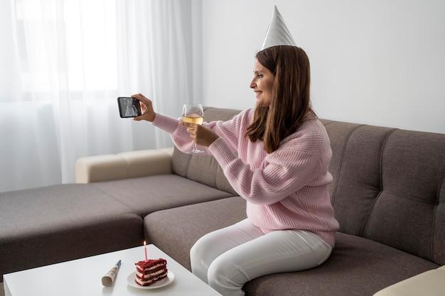 Mulher em quarentena comemorando aniversário por telefone