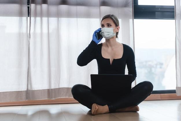 Mulher em quarentena corona com telefone e computador portátil