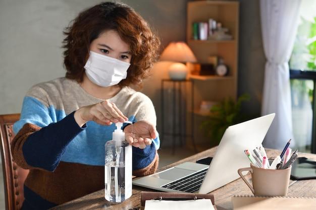 Mulher em quarentena e distanciamento social usando máscara cirúrgica e limpando as mãos com desinfetante em gel de álcool enquanto trabalhava em casa durante a pandemia de coronavírus covid-19