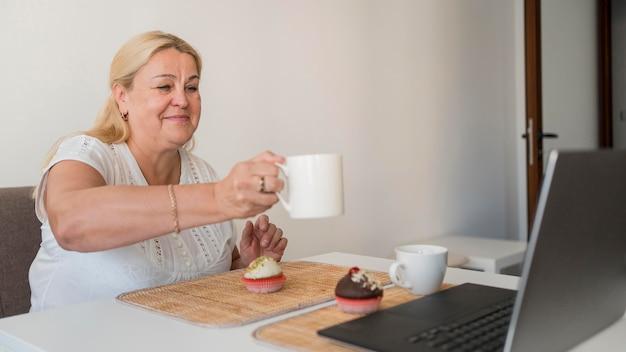 Mulher em quarentena tomando café com amigos no laptop