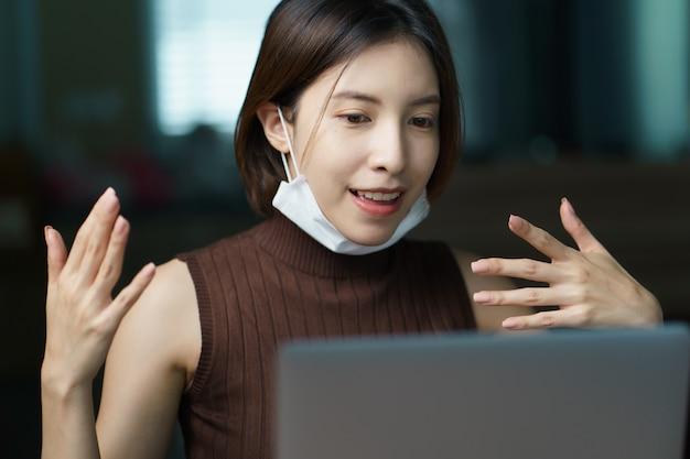 Mulher em quarentena usando máscara protetora trabalhando em casa durante o surto de coronavírus.