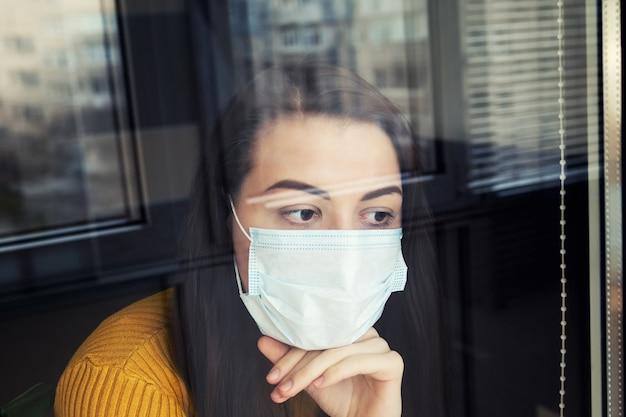 Mulher em quarentena, usando máscara protetora.