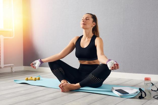 Mulher em roupa de ginástica fazendo exercícios em casa, hora para o conceito de ioga ficar em casa