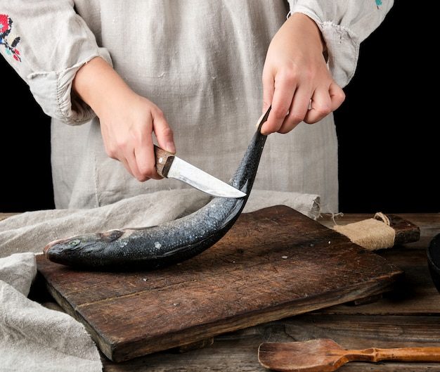 Mulher em roupa de linho cinza limpa o peixe robalo