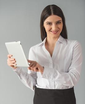 Mulher em roupa formal está usando um tablet digital