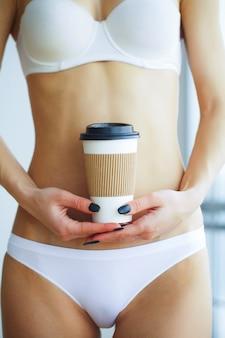 Mulher em roupa interior, segurando a xícara de café