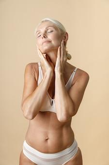 Mulher em roupa íntima com corpo em forma posando para a câmera e tocando a pele do rosto em pé isolado