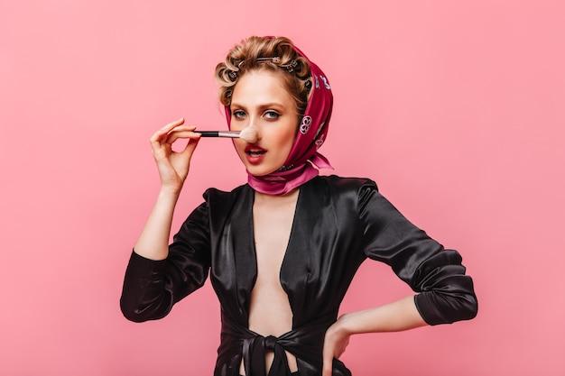 Mulher em roupão de seda e lenço rosa segurando um pincel de maquiagem e olhando para a frente