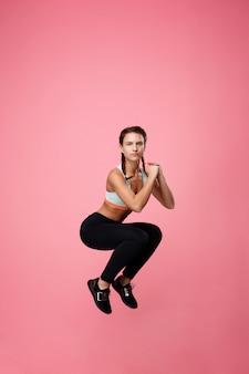 Mulher em roupas confortáveis de esporte pulando