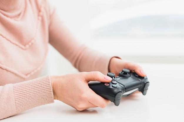 Mulher em roupas cor de rosa, jogando consola de jogos