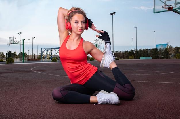 Mulher em roupas de esporte sagacidade fones de ouvido vermelhos, sentado no campo de basquete e fazendo treinamento de ginástica.
