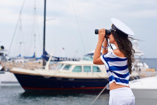 Mulher em roupas de estilo do mar olha para a distância através de binóculos