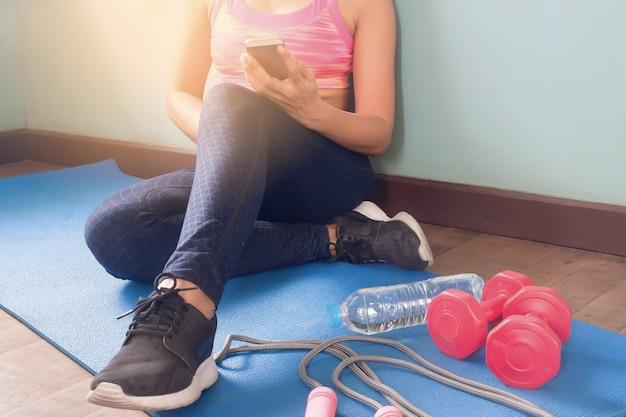 Mulher em roupas de fitness usando smartphone, estilo de vida saudável e conceito de treino