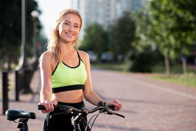 Mulher em roupas de ginástica e bicicleta no parque
