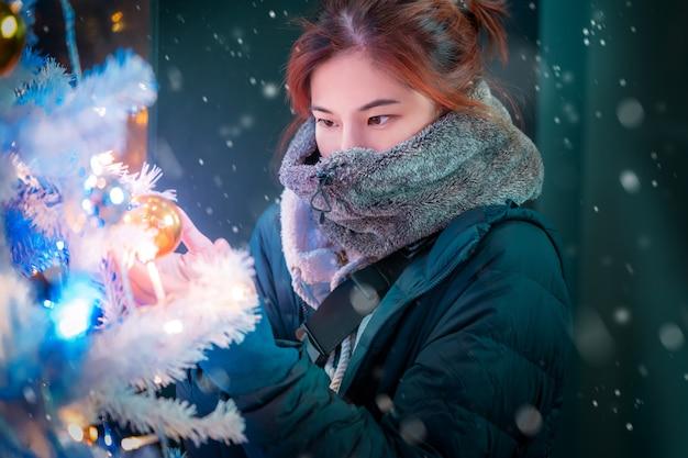 Mulher em roupas de inverno perto de uma árvore de natal