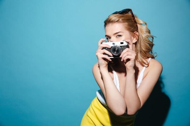 Mulher em roupas de verão, tirando foto na câmera retro