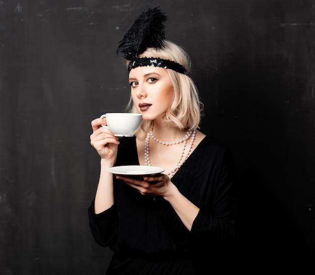Mulher em roupas de vinte anos com uma xícara de café