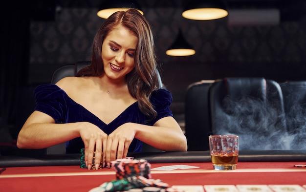 Mulher em roupas elegantes senta-se no cassino por mesa e joga jogo de poker
