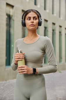 Mulher em roupas esportivas bebe água após o treino se mantém hidratada passeios na cidade pensa em novo programa de condicionamento físico ouve música relaxante no fone de ouvido