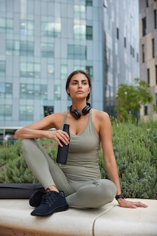Mulher em roupas esportivas bebe água sente sede após o treinamento físico usa fones de ouvido para ouvir poses de música em cityscrapers faz uma pausa durante o treino. estilo de vida saudável