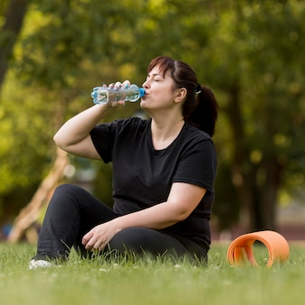 Mulher em roupas esportivas bebendo água