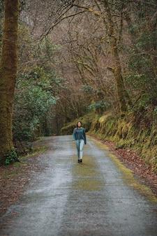 Mulher em roupas esportivas caminhando ao longo da estrada de asfalto na floresta durante o treinamento cardiovascular