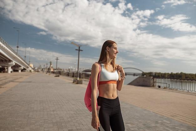 Mulher em roupas esportivas com mochila rosa fica na margem da cidade moderna